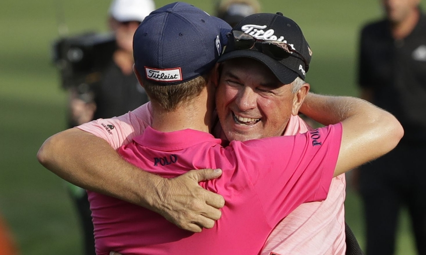Justin Thomas hugs his father, Mike